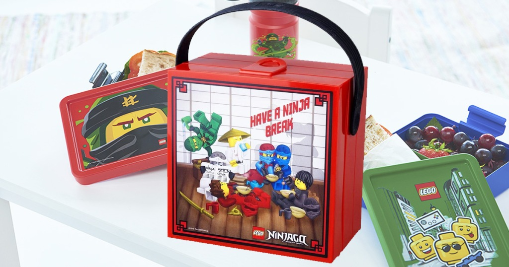 square red LEGO Ninjago lunchbox with other LEGO lunchboxes on table behind it