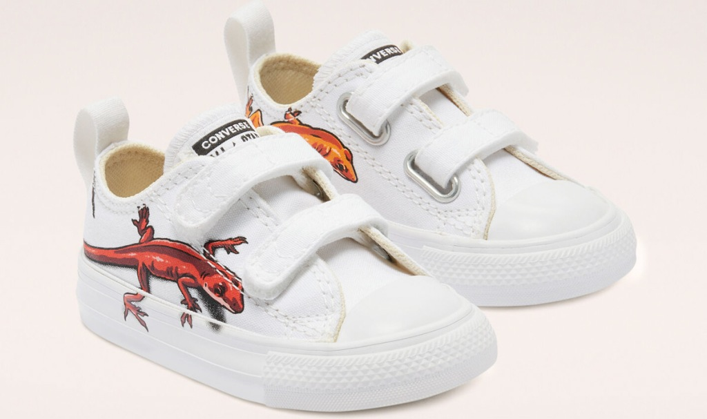 white toddler converse shoes with velcro straps and red and orange lizards on the sides