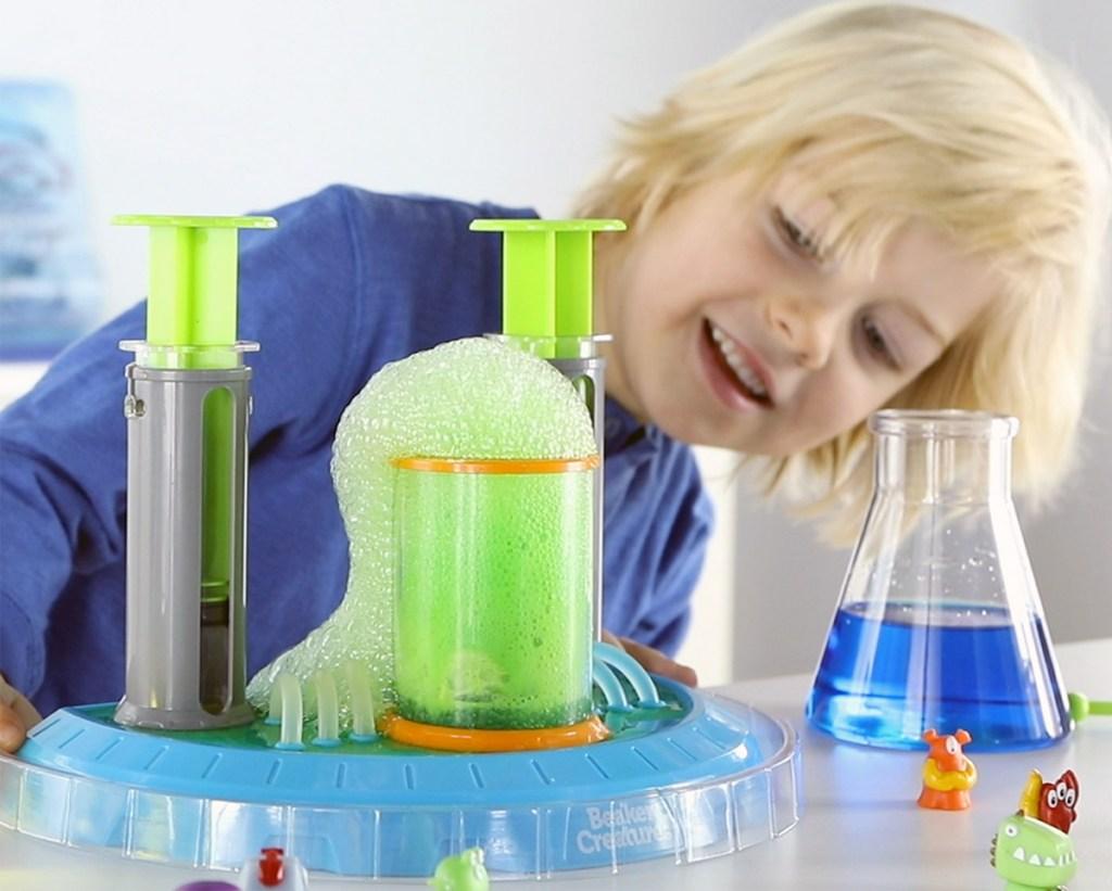 boy in blue shirt watching a green colored foam reaction happen inside lab beaker play set