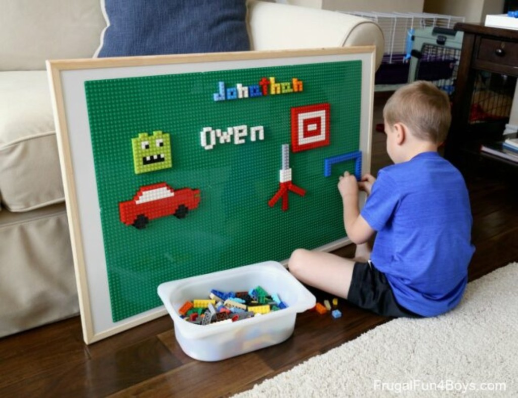 boy adding Lego pieces to vertical play surface