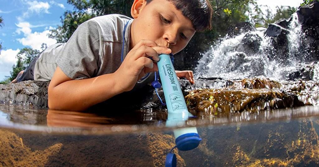 anak laki-laki berbaring untuk menempelkan gaya hidup biru ke sungai untuk minum