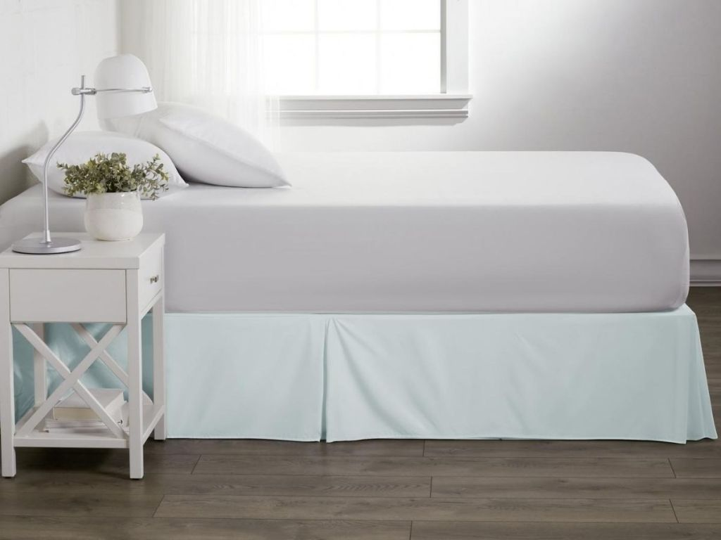 unmade bed with bed skirt and end table