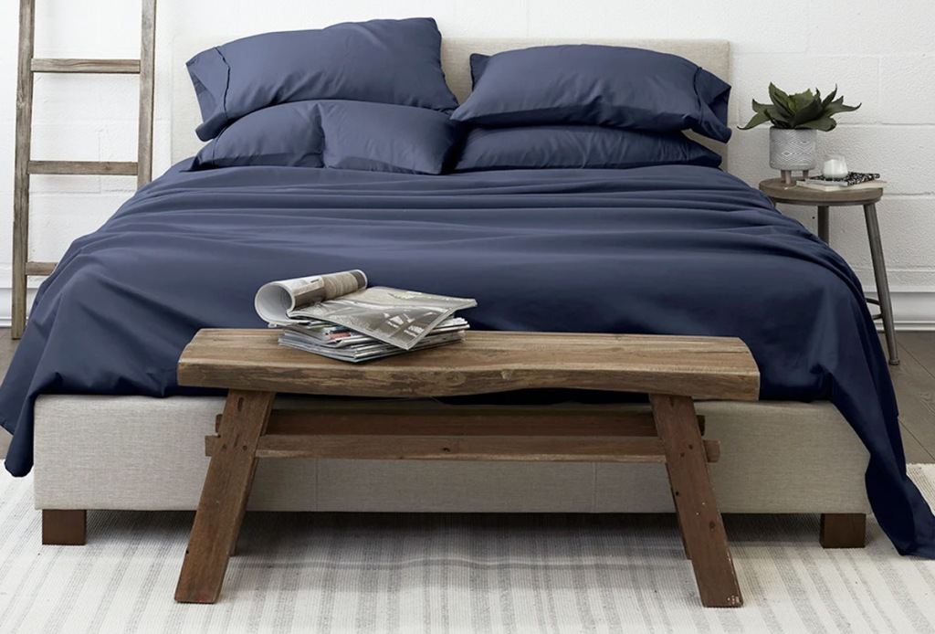 navy blue sheet set on bed with wood table at foot of bed
