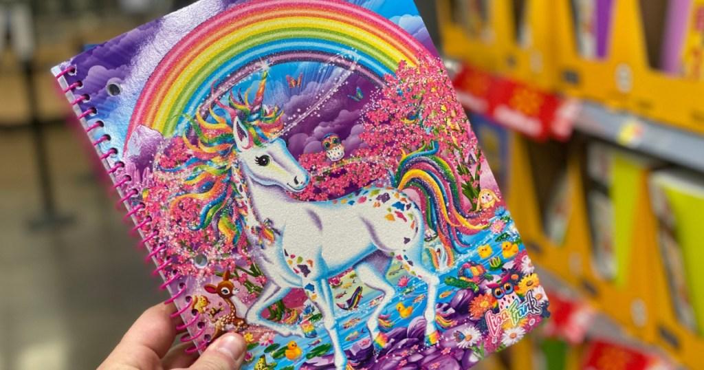 hand holding Lisa Frank Unicorn and rainbow notebook