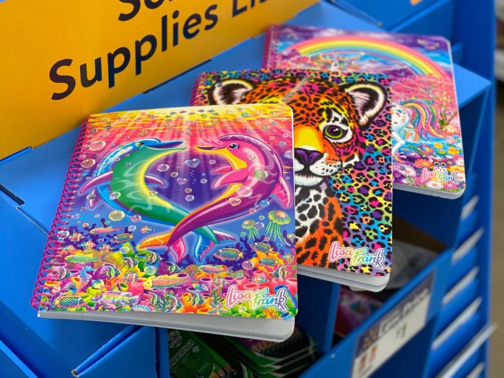 3 brightly colored Lisa Frank notebooks sitting on walmart store shelf