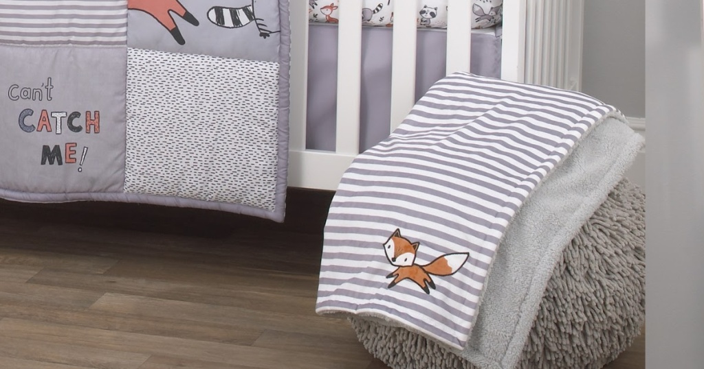 grey and white striped baby blanket with a fox laying on a fuzzy foot rest