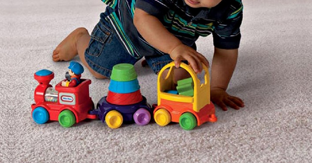 young boy playing with toy train and stack set on carpet