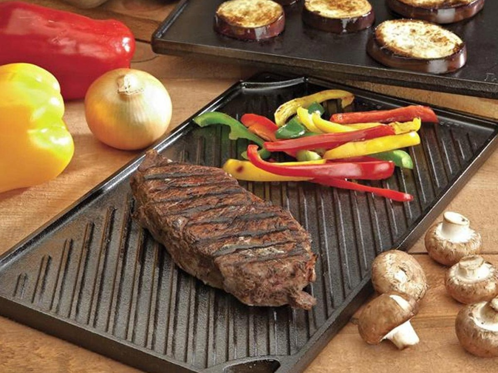 steaks and peppers on grill/griddle on counter