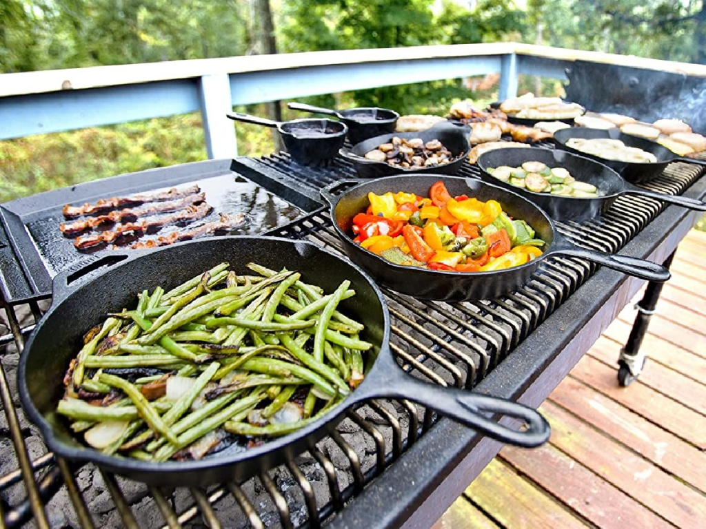 cast iron grill pans filled with food on outdoor grill