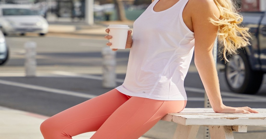 woman holding coffee and leaning against wood picnic table wearing white tank top and pink leggings