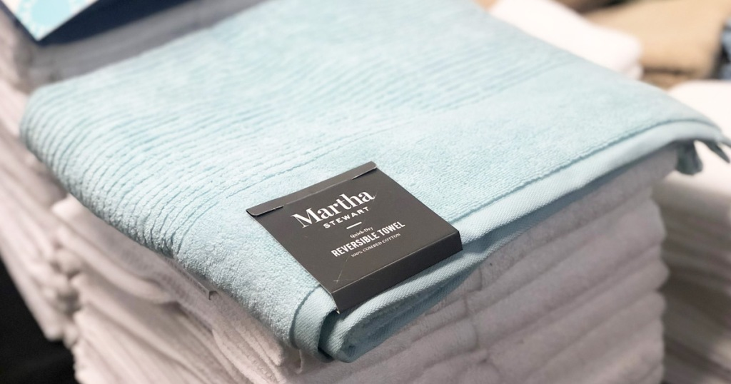 light blue Martha Stewart quick-dry bath towel on top of stack of folded white towels