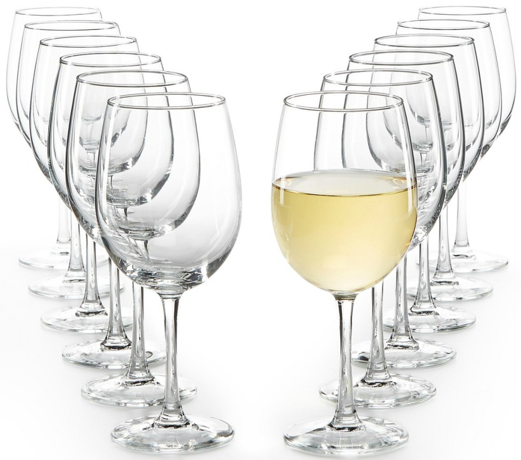 A dozen white wine glasses with one filled
