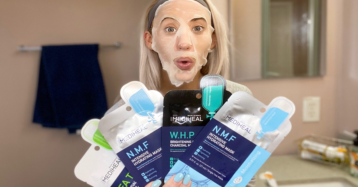 woman with a facial sheet mask on her face holding up four other packets of sheet masks