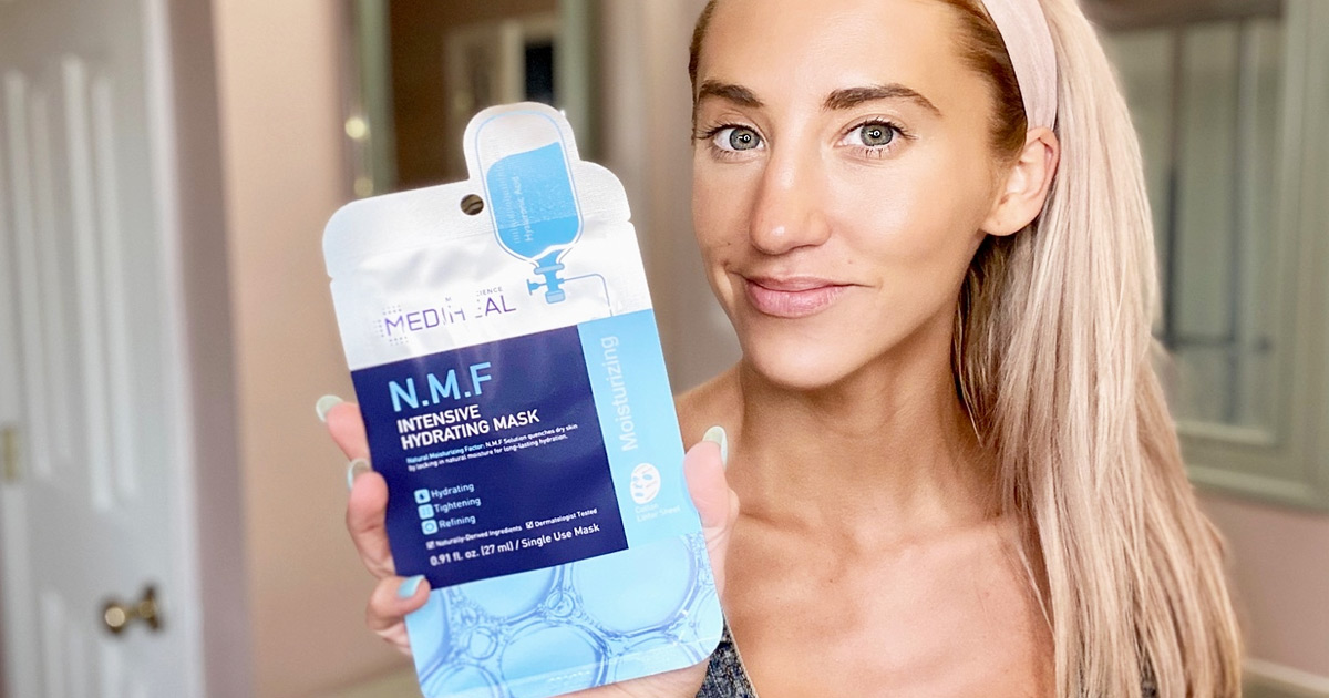 woman with blonde hair holding up a blue package of Mediheal facial sheet mask next to her face