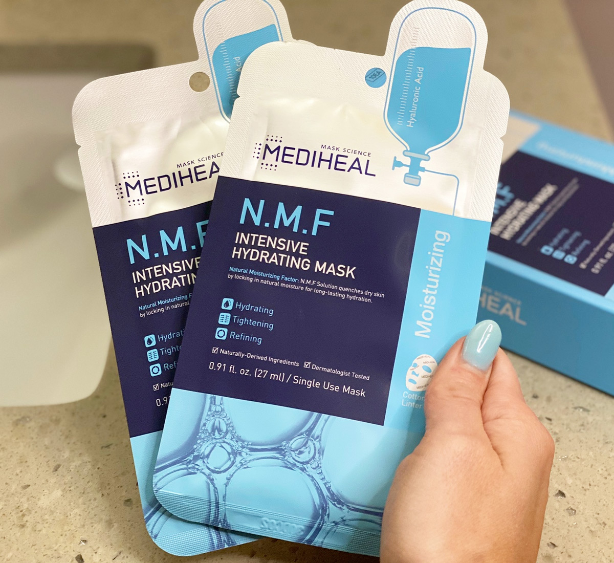 woman with blue finger nails holding up two Mediheal brand facial sheet masks