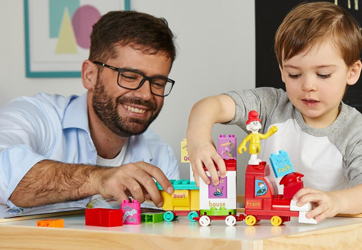 boy and man playing with Dr. Seuss train building set on table