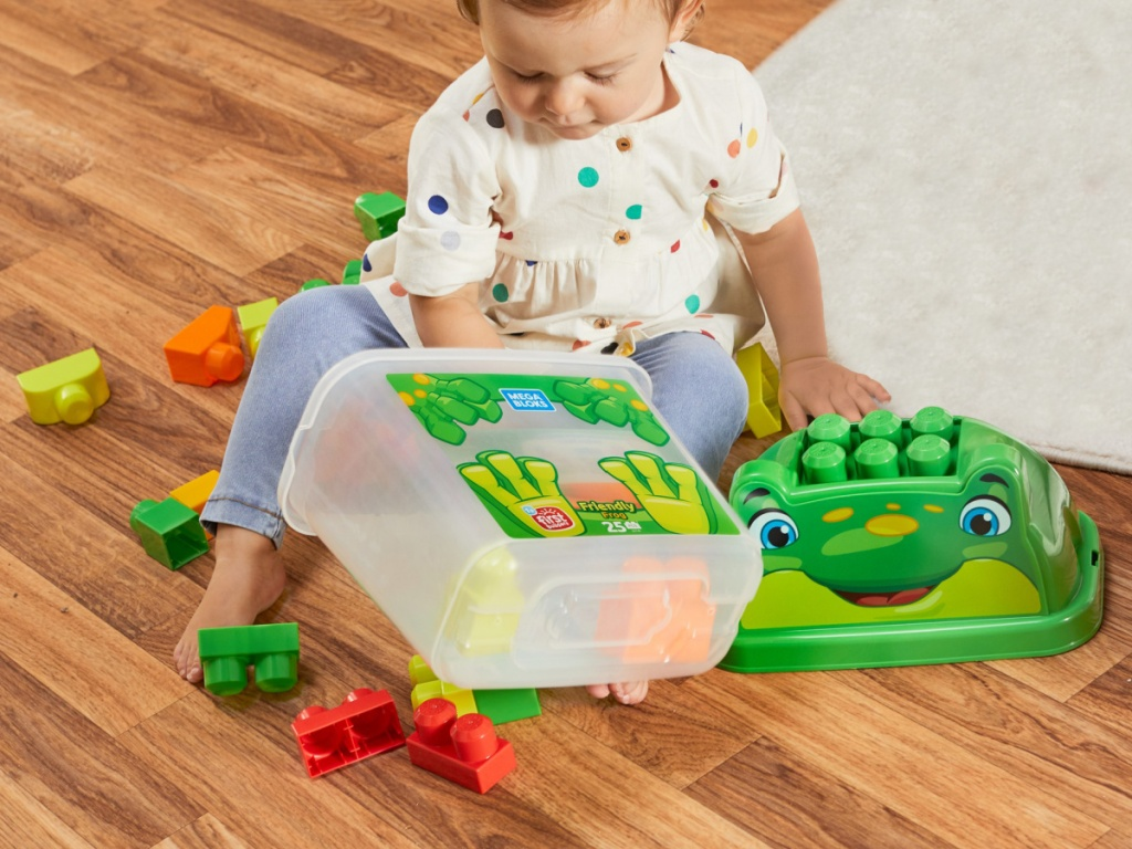 young girl playing with frog building block set on living room floor