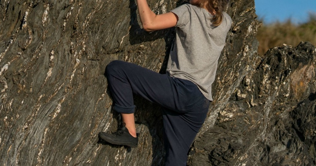 woman climbing rock face wearing hiking shoes