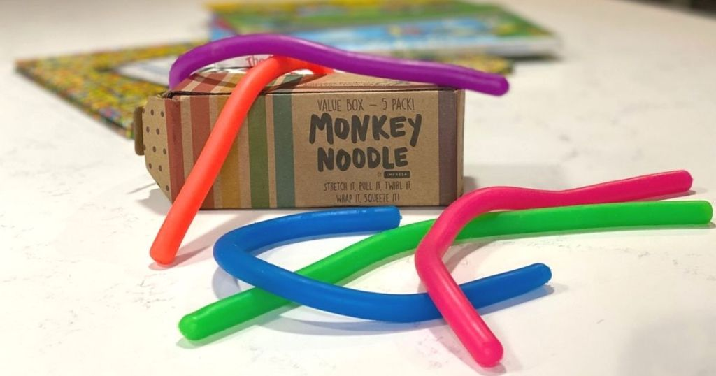 stretchy monkey noodle sensory toys on a counter next to the box