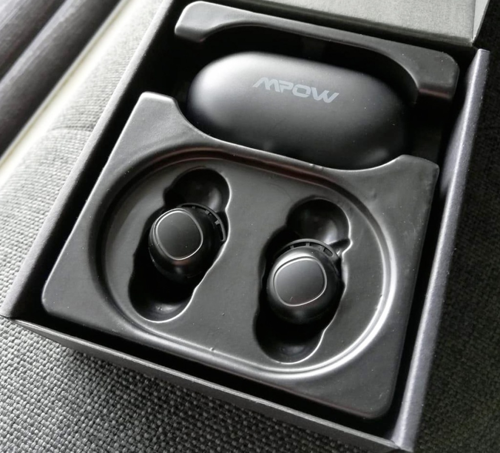 black wireless earbuds with charging case inside of box on grey couch