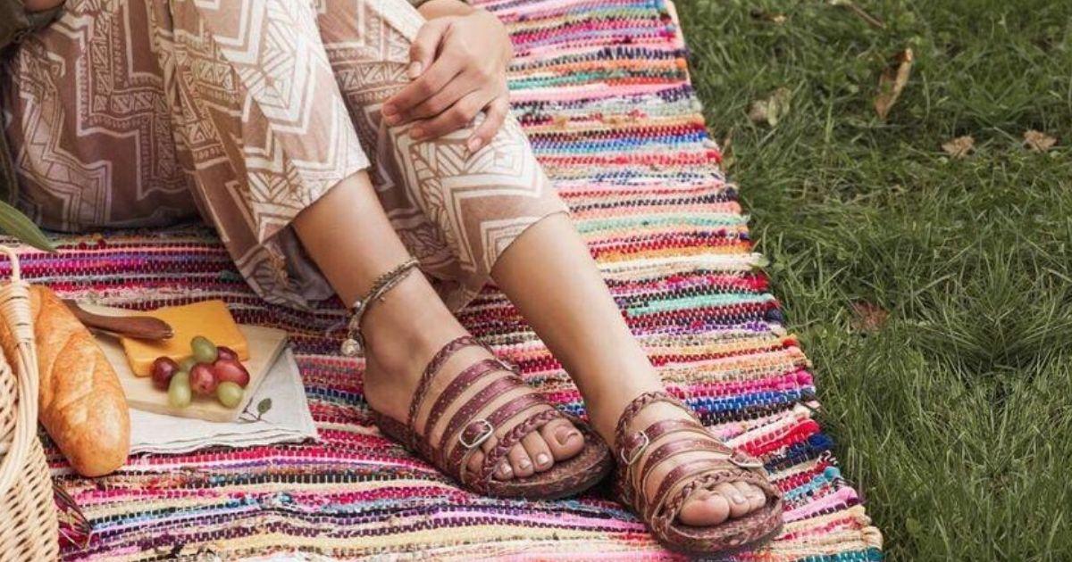 woman sitting on blanket wearing sandals