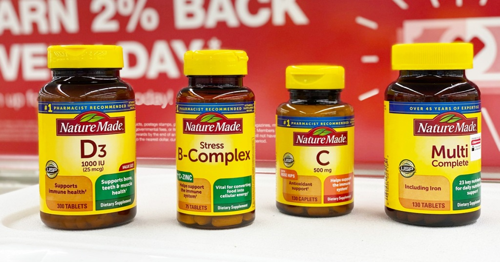 four brown and yellow bottles of Nature Made vitamins on CVS store shelf
