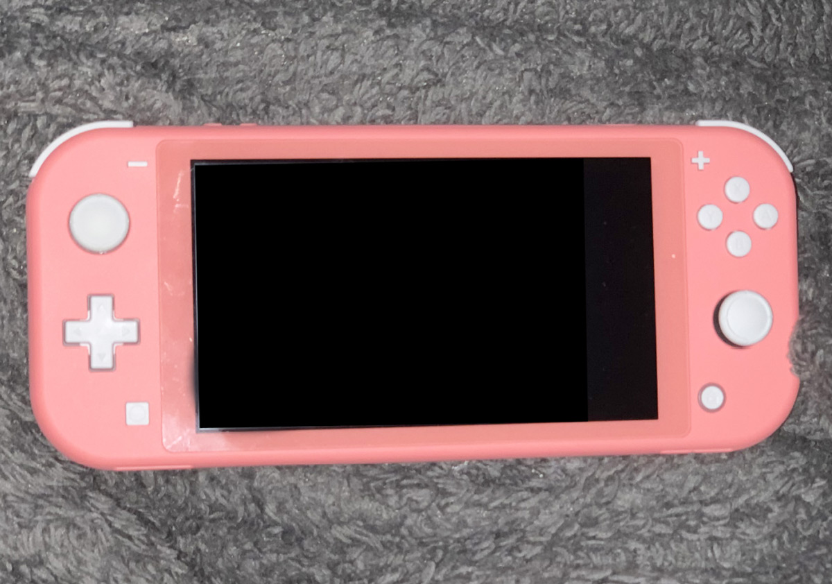 pink nintendo switch with white buttons laying on a grey fuzzy blanket