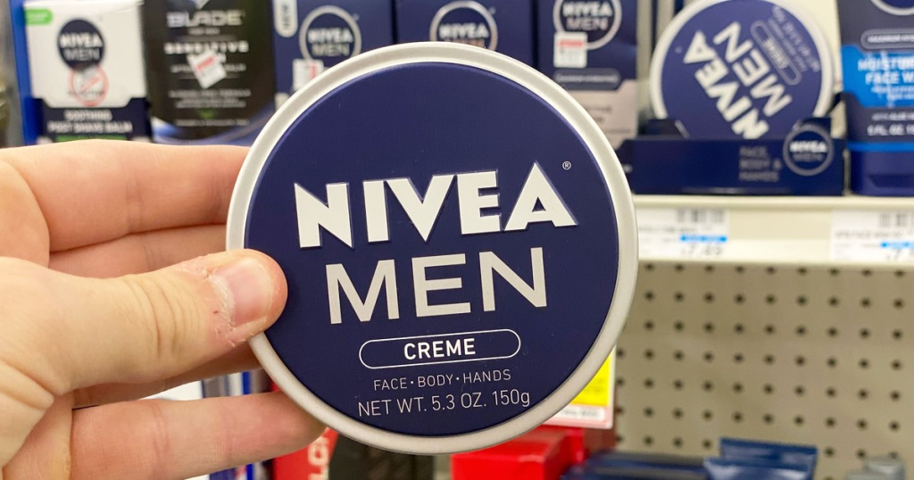 man holding up a blue colored round tin of Nivea Men's face and body creme
