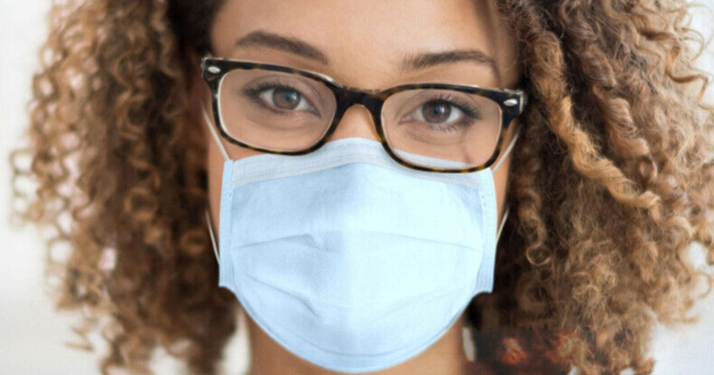 woman wearing glasses and a light blue non medical face mask
