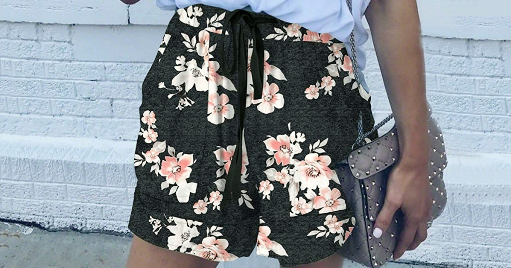 woman modeling pair of loose fitting black shorts with white and pink floral print