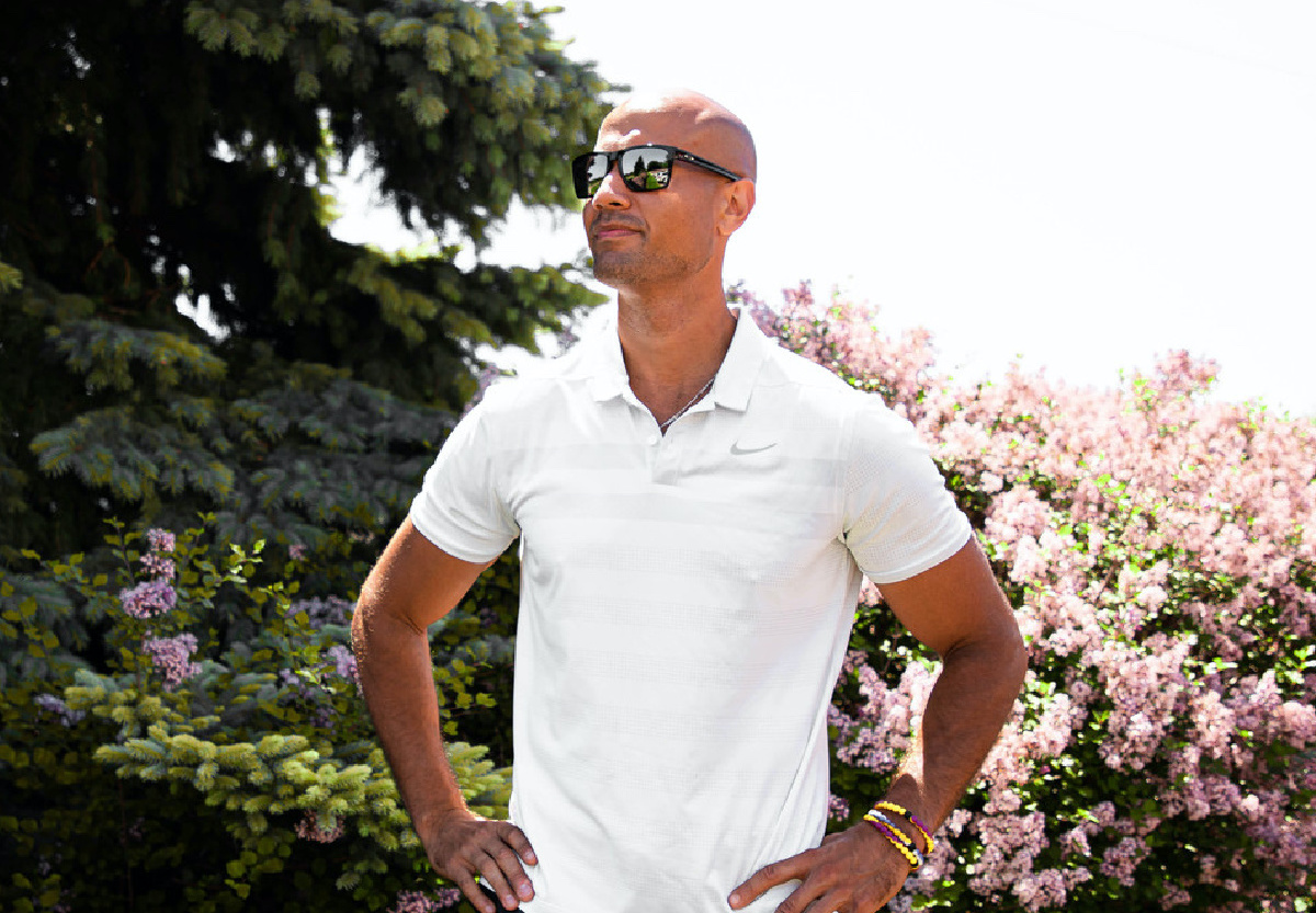 man in black sunglasses outside with foliage in background