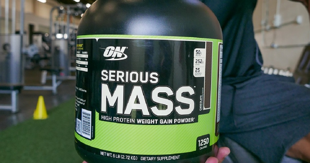 person holding large container of chocolate protein powder in gym