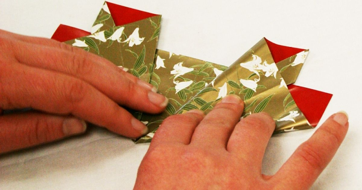 woman's hands folding origami