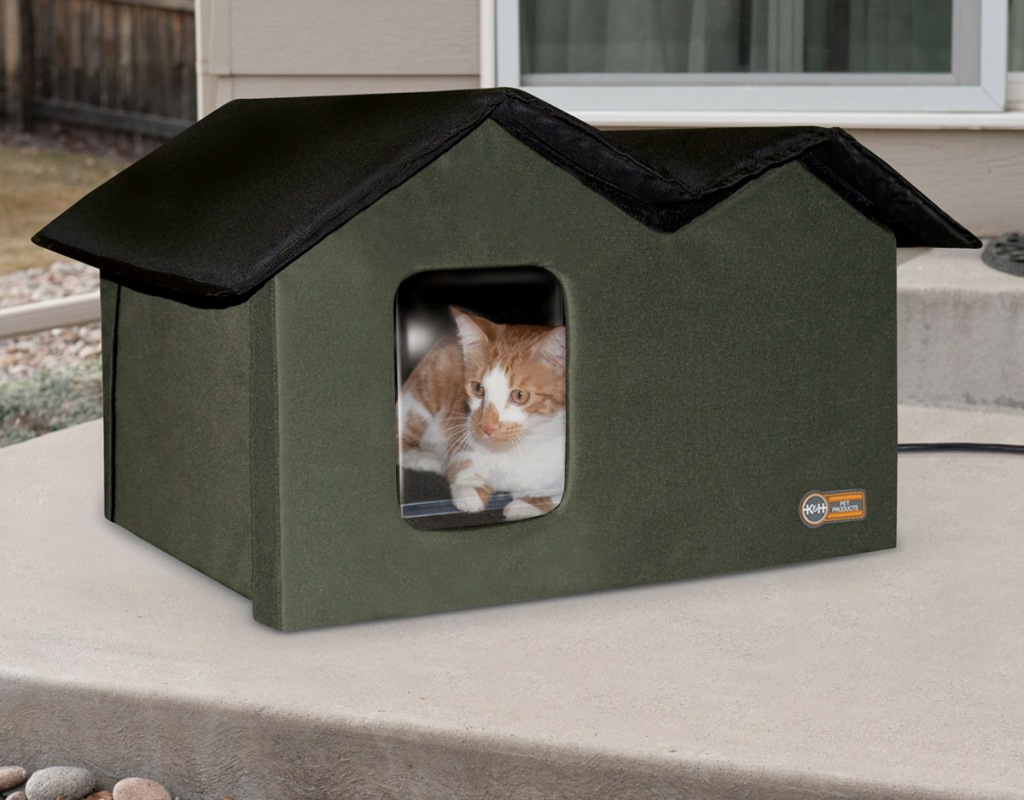 olive green cat house with black roof on outdoor patio with orange and white cat inside