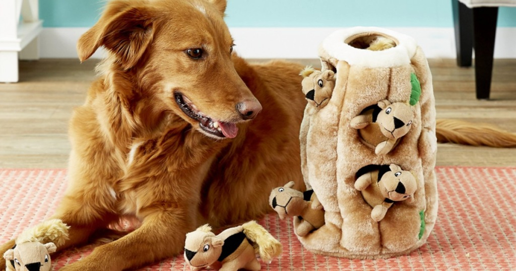 golden retriever playing with large squirrels in tree stump stuffed toy