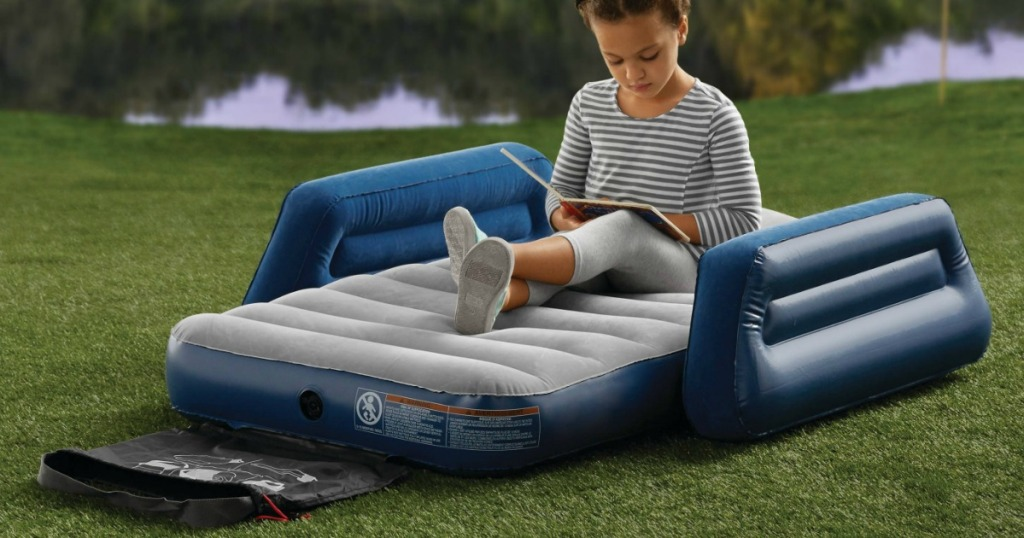 Young girl reading a book sitting on an air mattress in the grass