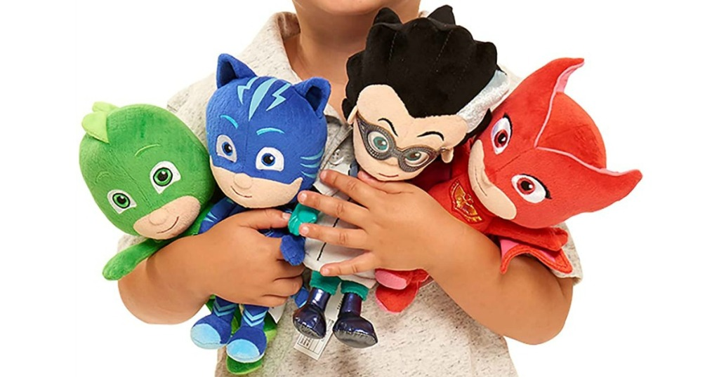 child holding PJ Masks plush toys