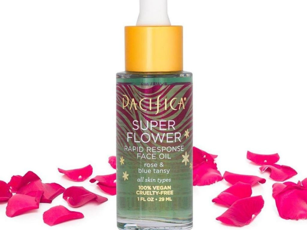 bottle of skincare oil with rose petals