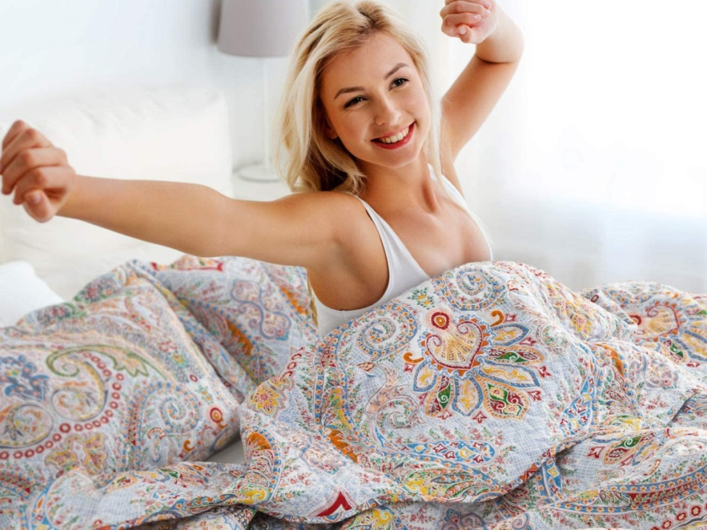 woman sitting up in bed stretching surrounded by bright paisley bedding