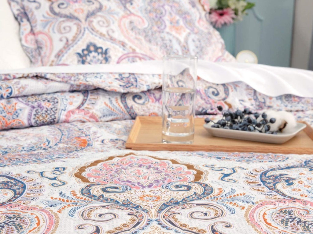 wooden tray with a glass of water and fresh blueberries sitting on top of paisley bedding