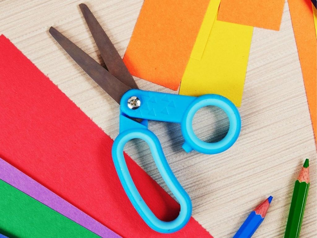 kid's scissors next to construction paper and colored pencils