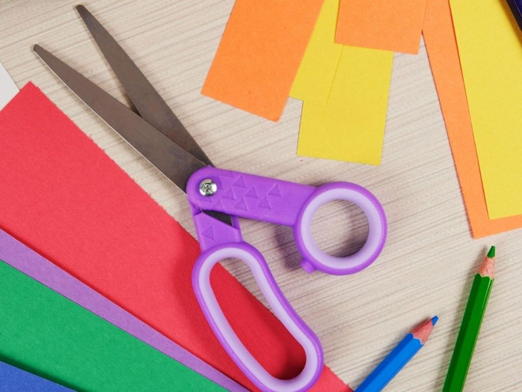 children's scissors next to construction paper and colored pencils