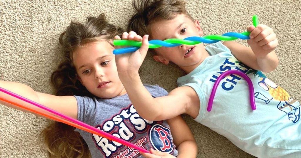 Two kids playing with stretchy toys on the floor