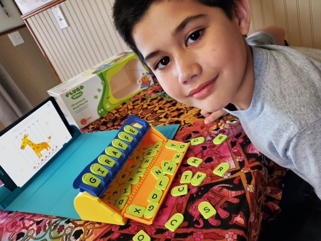 boy playing with Plugo Letters Word Building with Stories & Puzzles