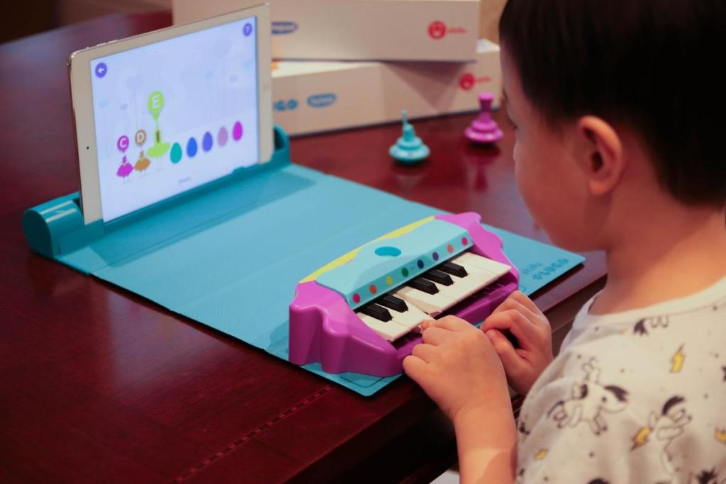 boy playing with Plugo Tunes Piano Learning Kit
