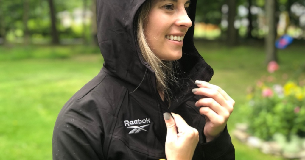 Women wearing a black Reebok coat with the hood pulled up