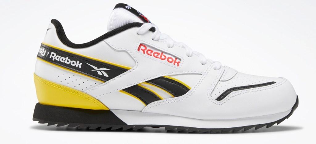 white, black, and yellow kids leather reebok shoe