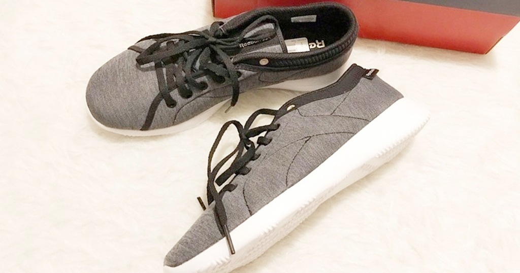 pair of black fabric womens reebok shoes laying next to red shoe box