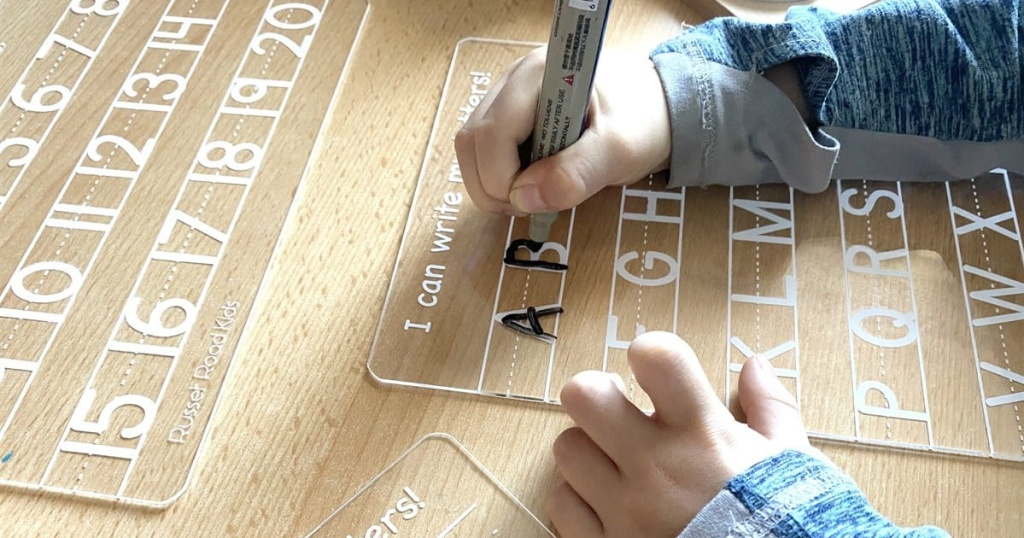 kids hands tracing over letters on wipe off board
