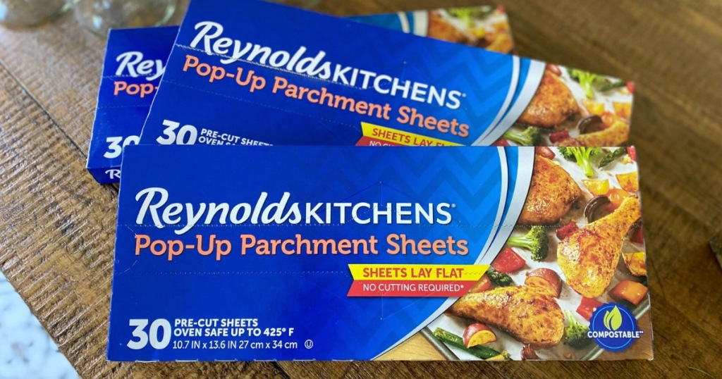 three blue boxes of reynolds parchment paper sheets on wood table